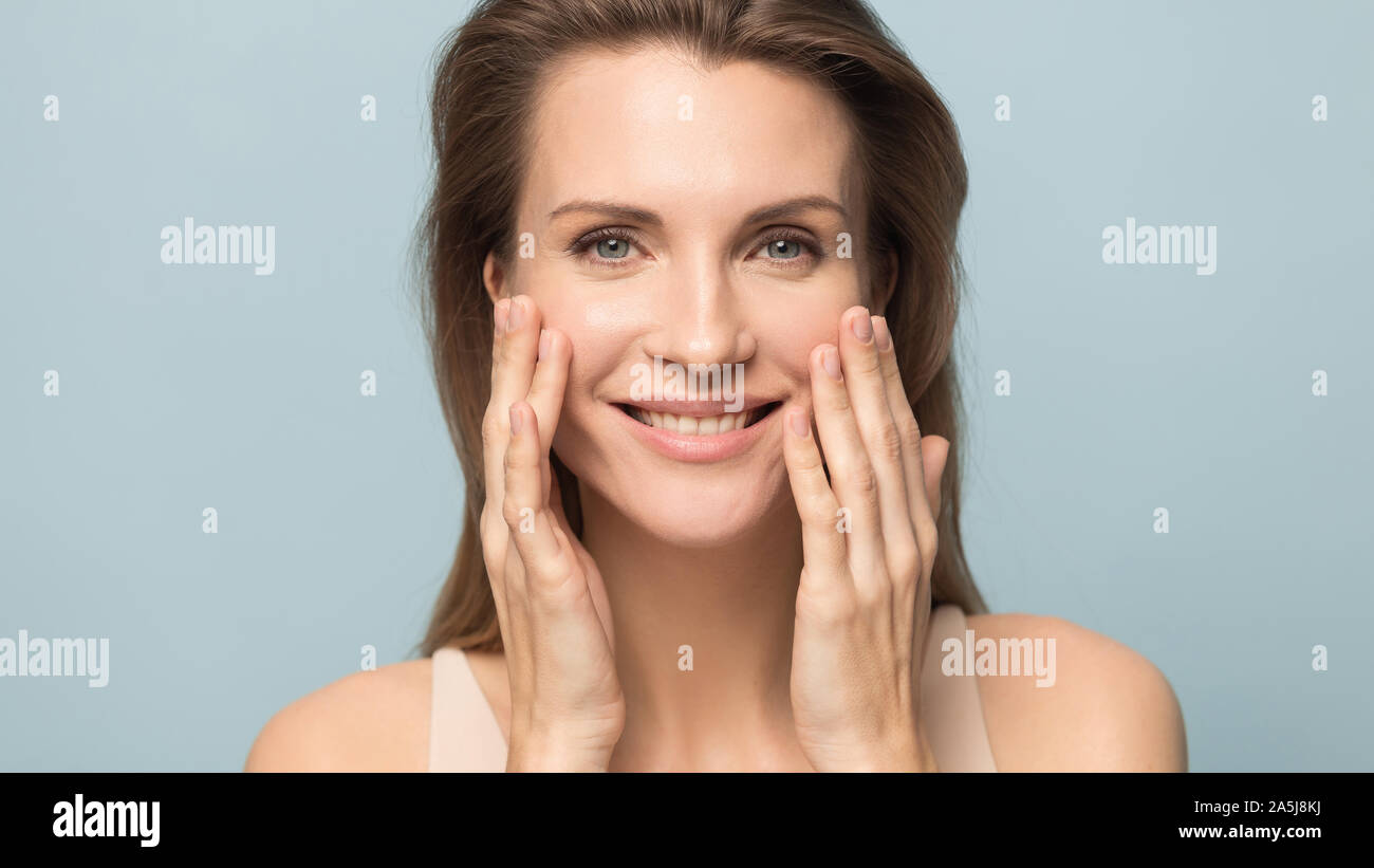 Smiling millennial woman touch healthy breathing skin Stock Photo