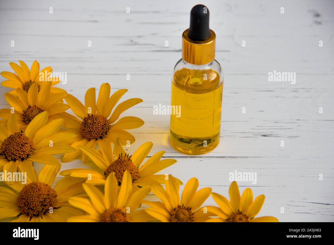 yellow flowers and cosmetic oil in a bottle on a wooden light background Stock Photo