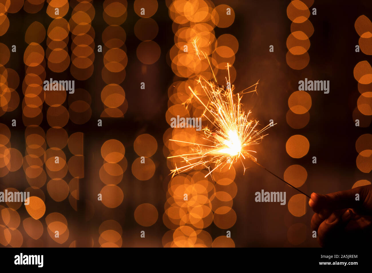 Abstract Sparkelrs background with light yellow bokeh, bright festive Diwali, Christmas, Happy New Year background stock image. Man Holding Sparkler. Stock Photo