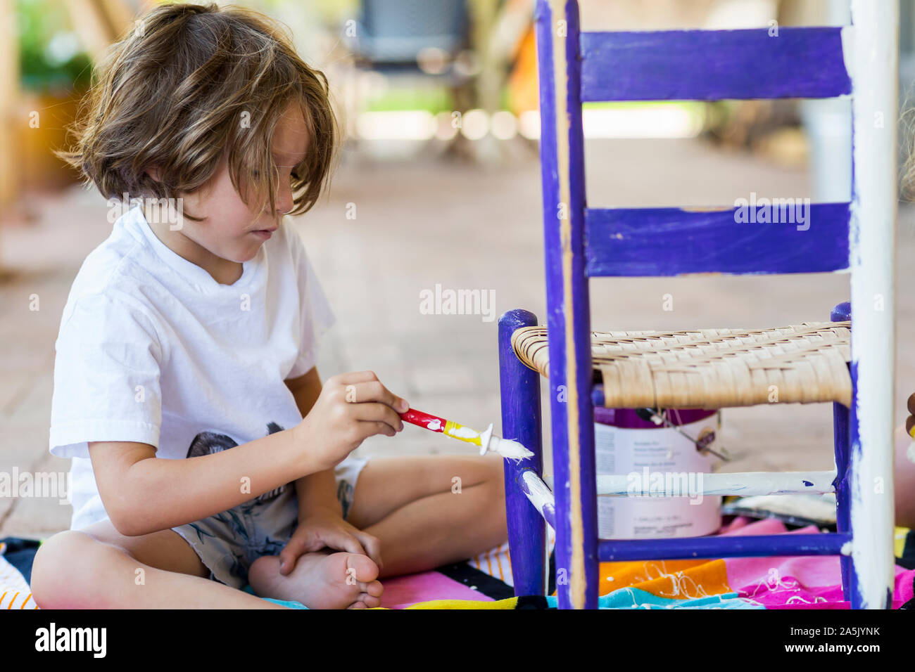 5 year old boy painting children's chair on porch with his sister Stock Photo