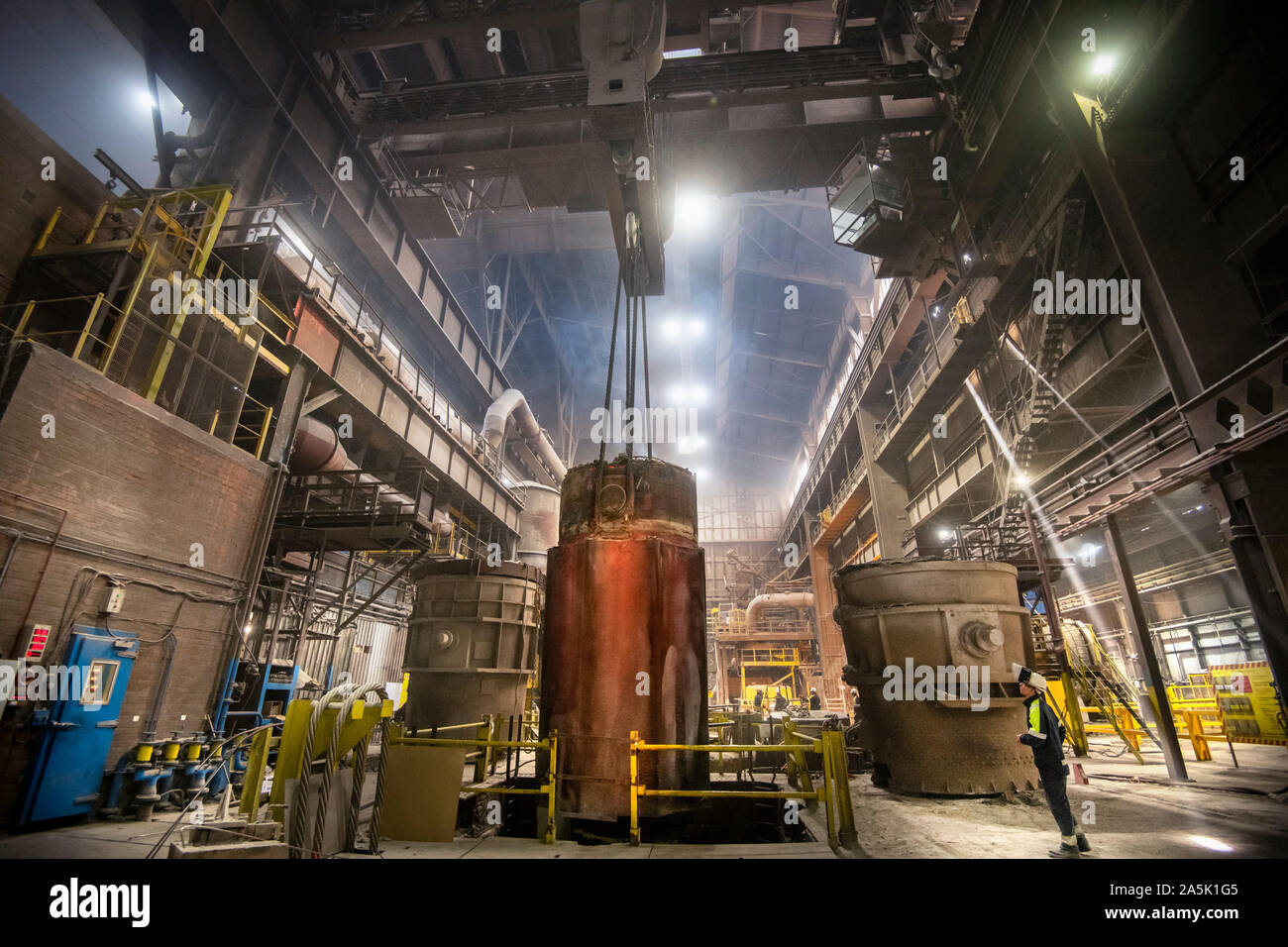 200 ton red hot steel ingot being lifted from mould in steelworks Stock Photo