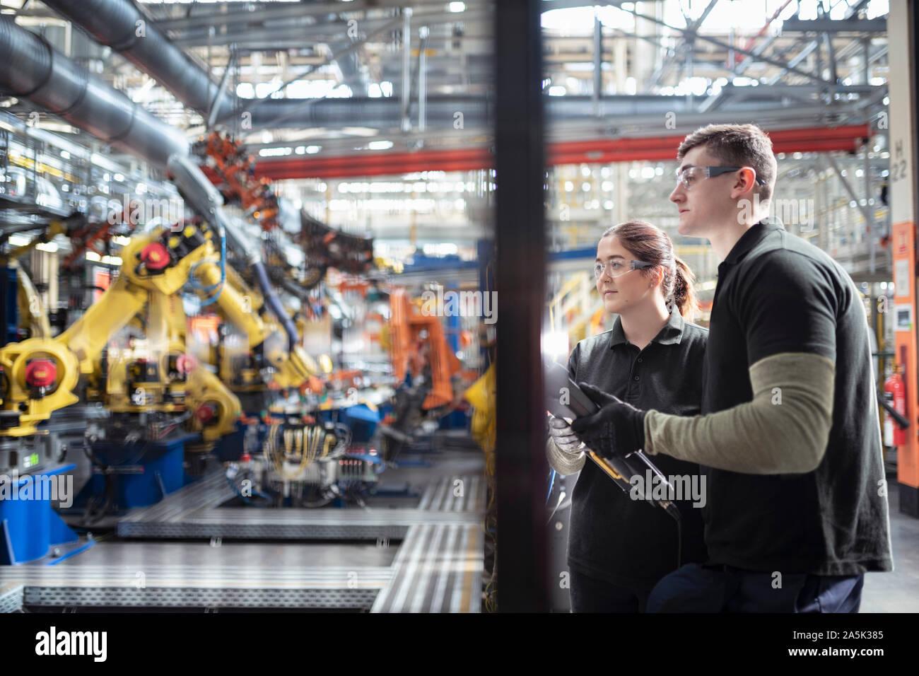 Apprentice engineers programming robots in car factory Stock Photo