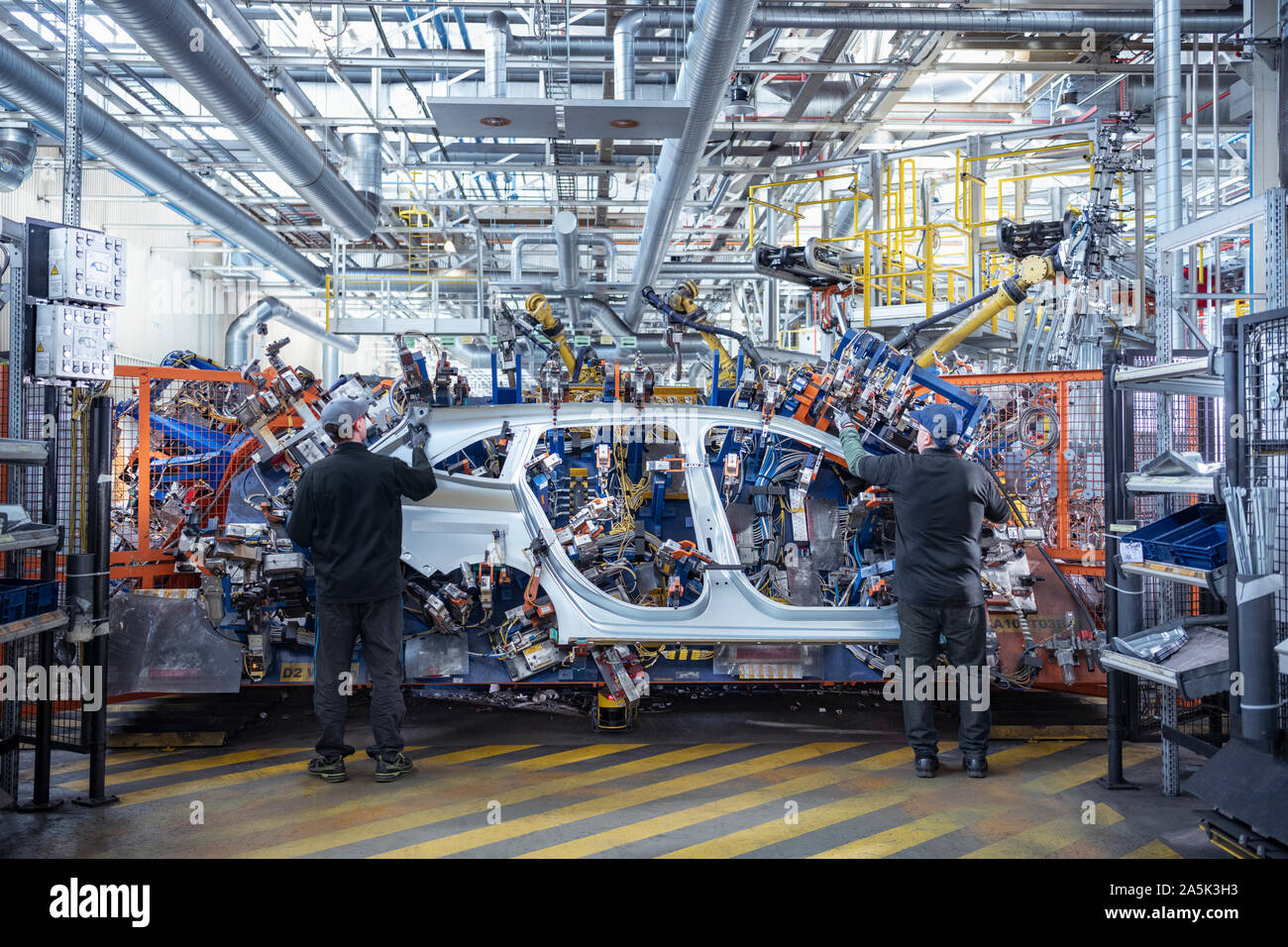 Workers loading car body spot welding machine with robots in car factory Stock Photo