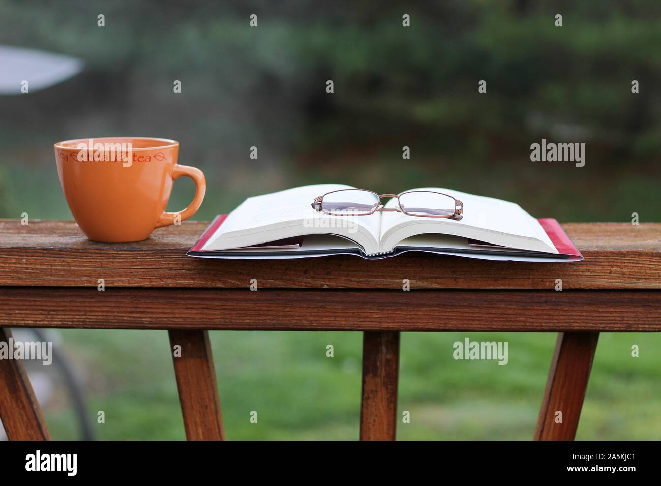 A pair of reading glasses on top of a book and a cup of tea outside on a deck Stock Photo