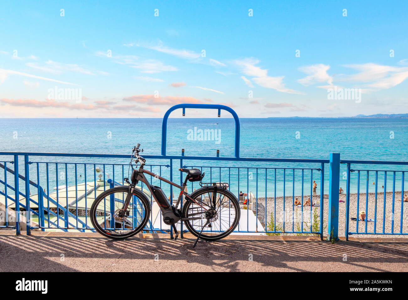 A bicycle is parked against a railing on the Promenade des Anglais with the Turquoise waters of the Bay of Angles behind in Nice, France. Stock Photo