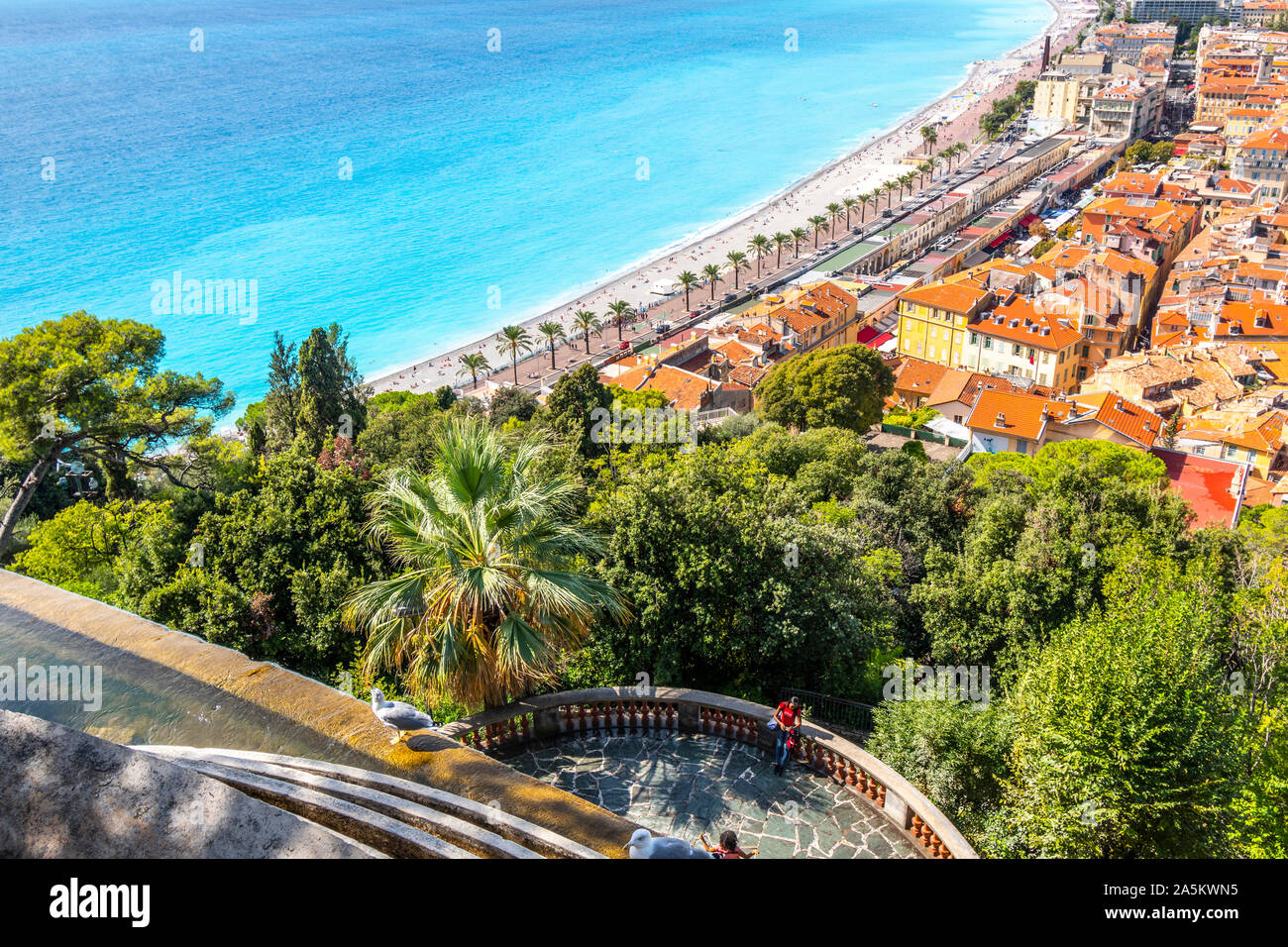 A female tourist on Castle Hill relaxes on a deck under the waterfall and above the Old Town, beach and promenade of Nice, France. Stock Photo