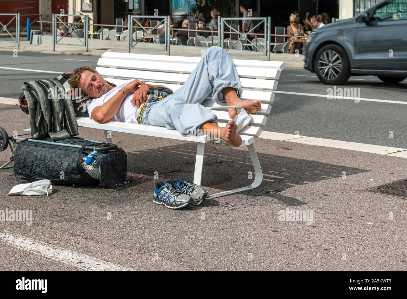 A tired male adult traveler sleeps on a bench on the Promenade des Anglais in the Mediterranean city of Nice, France. Stock Photo