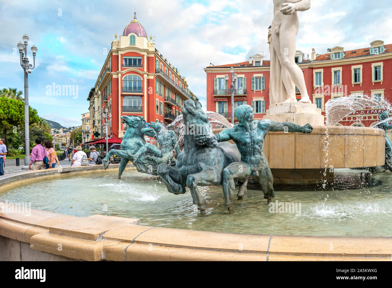 Tourists pass by the Fountain of the Sun with Roman God Apollo at Place Massena in the Mediterranean city of Nice, France. Stock Photo