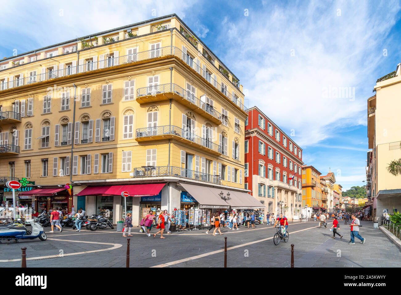 Tourists enjoy a wide colorful street of shops, markets and cafes leading to Old Town in the Mediterranean city of Nice, France. Stock Photo