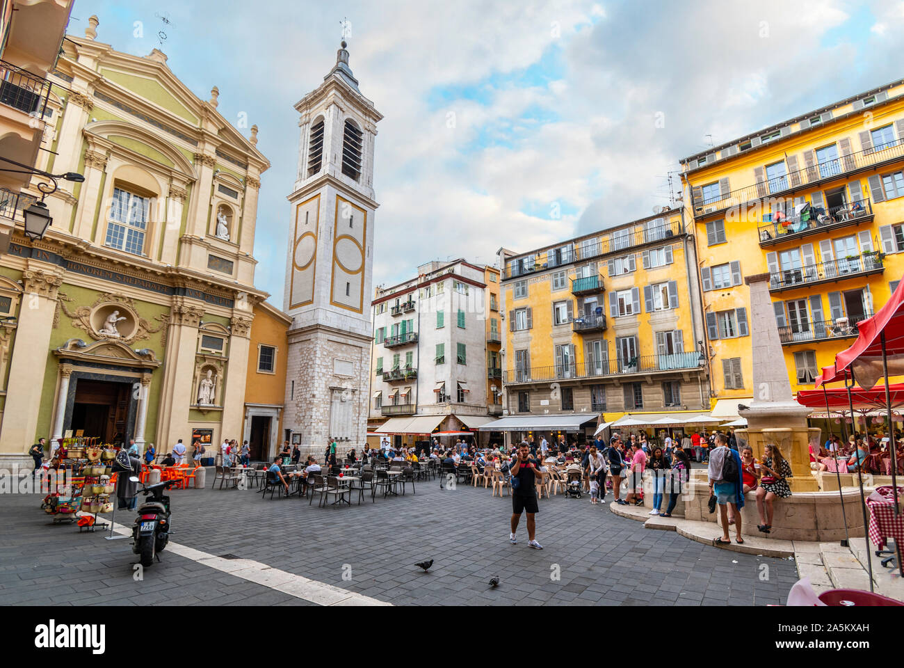 Tourists enjoy an early evening in Place Rossetti surrounded by shops, cafes, fountains and the Nice Cathedral, in Old Town Nice France. Stock Photo