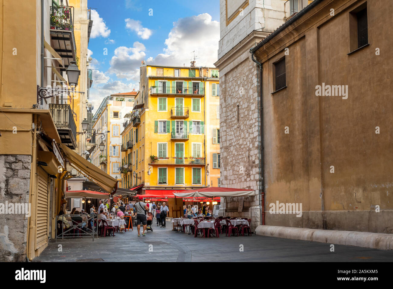 Tourists enjoy a lively late afternoon at the shops and cafes in Place Rossetti, in the old town center of Nice, France, on the French Riviera. Stock Photo