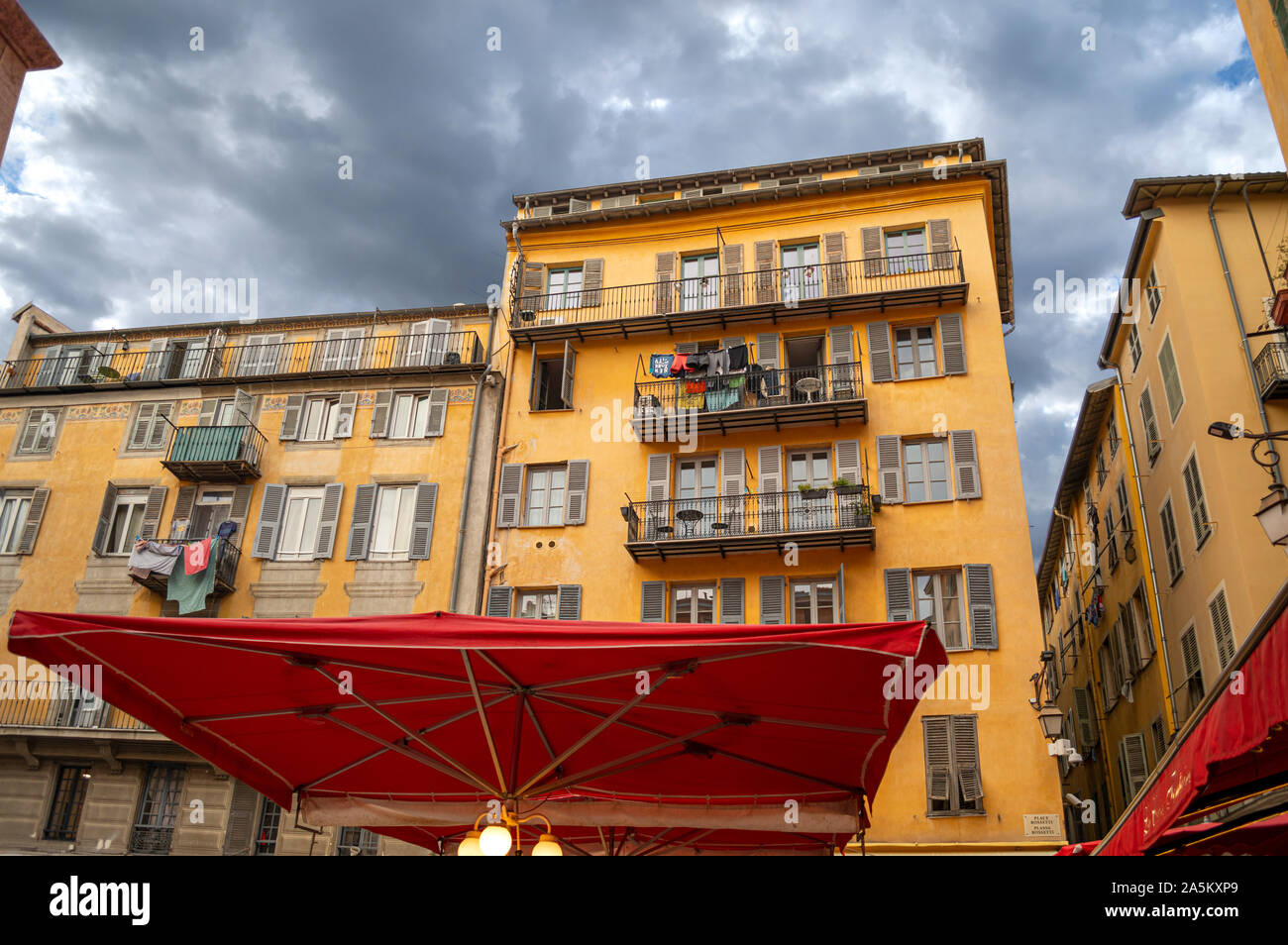 Dark clouds over Place Rossetti in Nice France as laundry hangs on balconies in the historic Old Vieux Nice Stock Photo