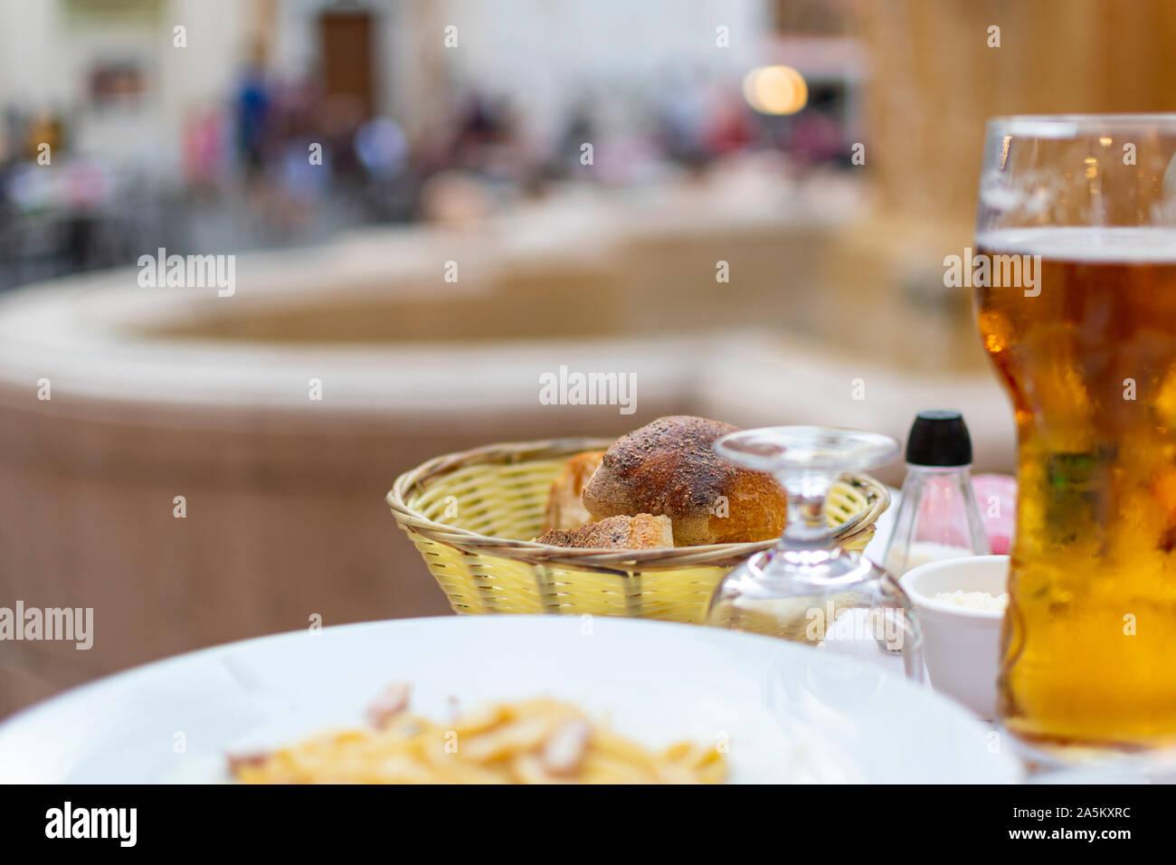 A bread basket of freshly baked rolls on a patio table in a piazza at Place Rossetti on the French Riviera in Nice, France. Stock Photo