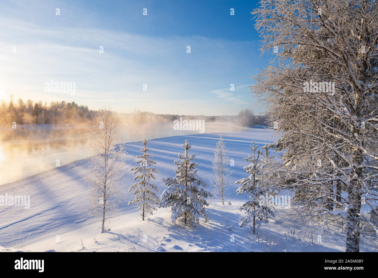 Mist over freezing river on a sunny cold winter day. Trees covered with frost and snow. Stock Photo