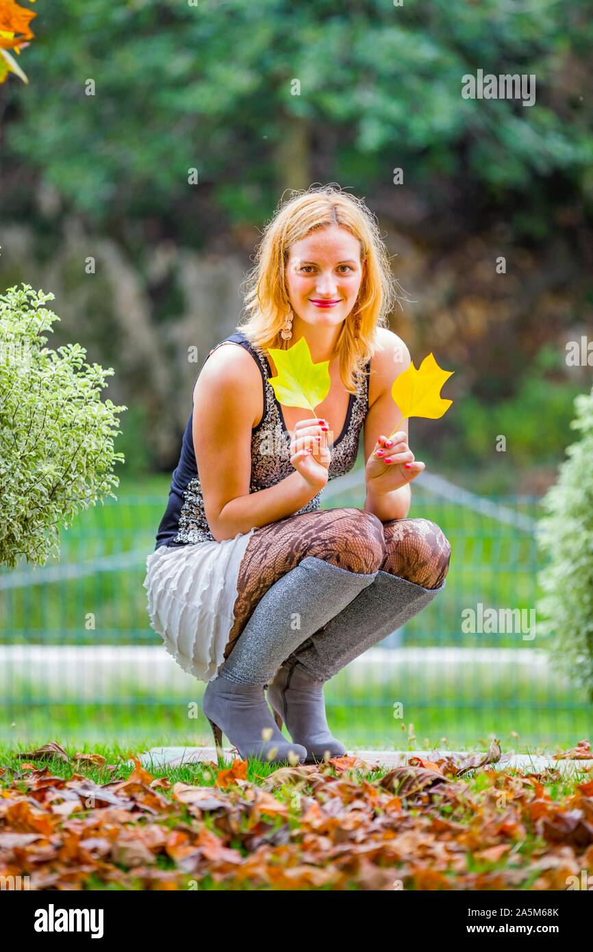 Mid-adult young woman blonde fairhair squatting amongst Autumn Fall fallen leaves in park and hand hands holding two leaves looking at camera eyeshot Stock Photo