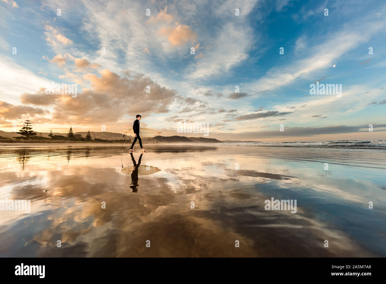 Teen with surfboard on a beach in New Zealand at sunset Stock Photo