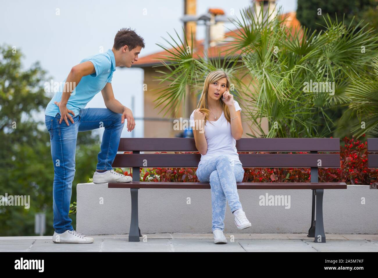 Endless chat female teenager long lengthy neverending talking on smartphone while her boyfriend friend waits nervously Stock Photo