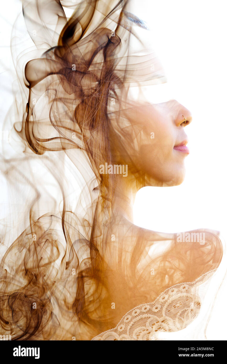 Double exposure. Photograph of smoke combined with a close up profile portrait of a beautiful young girl with back and shoulder facing the camera Stock Photo