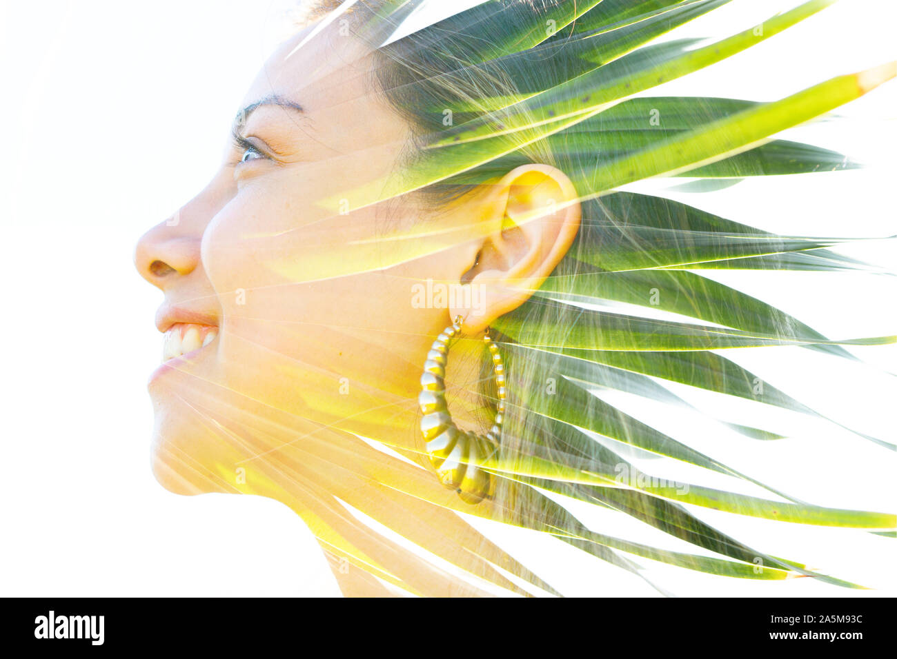 Double exposure profile portrait of a young, relaxed natural beauty large golden earrings and long brown hair combined with green tropical leaves on a Stock Photo