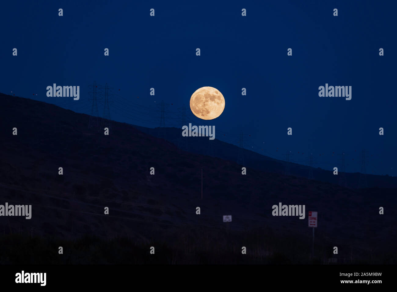 Full Moon rise over mountains at San Onofre beach, San Clemente, Southern California Stock Photo