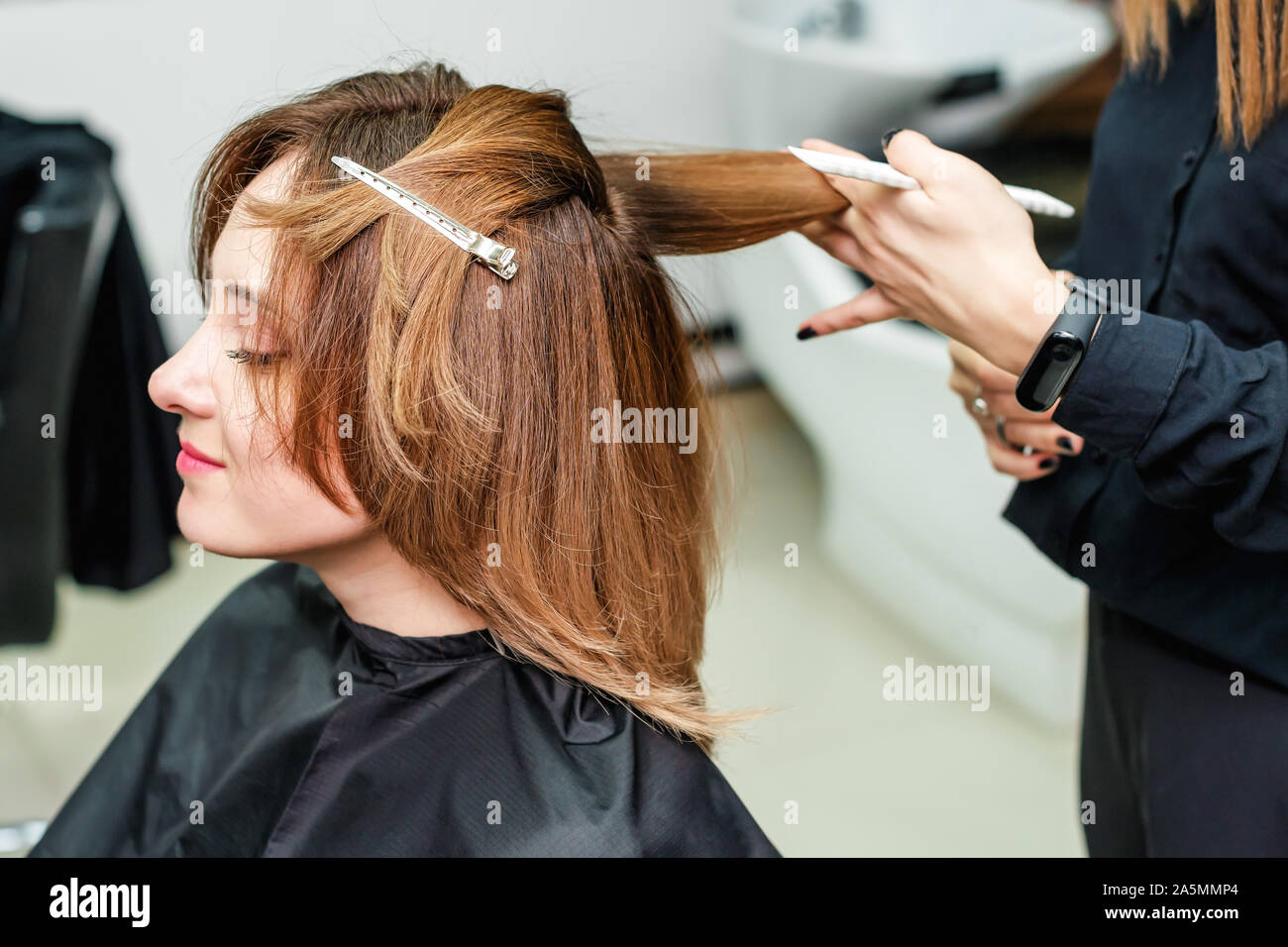 Woman hairdresser is making hairstyle to red hair girl in beauty salon. The process of hair styling in the hairdressing salon. Stock Photo