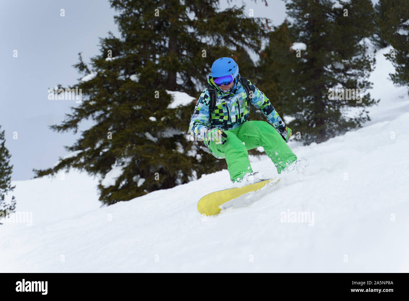 Male snowboarder riding on mountainside on background of trees in afternoon Stock Photo