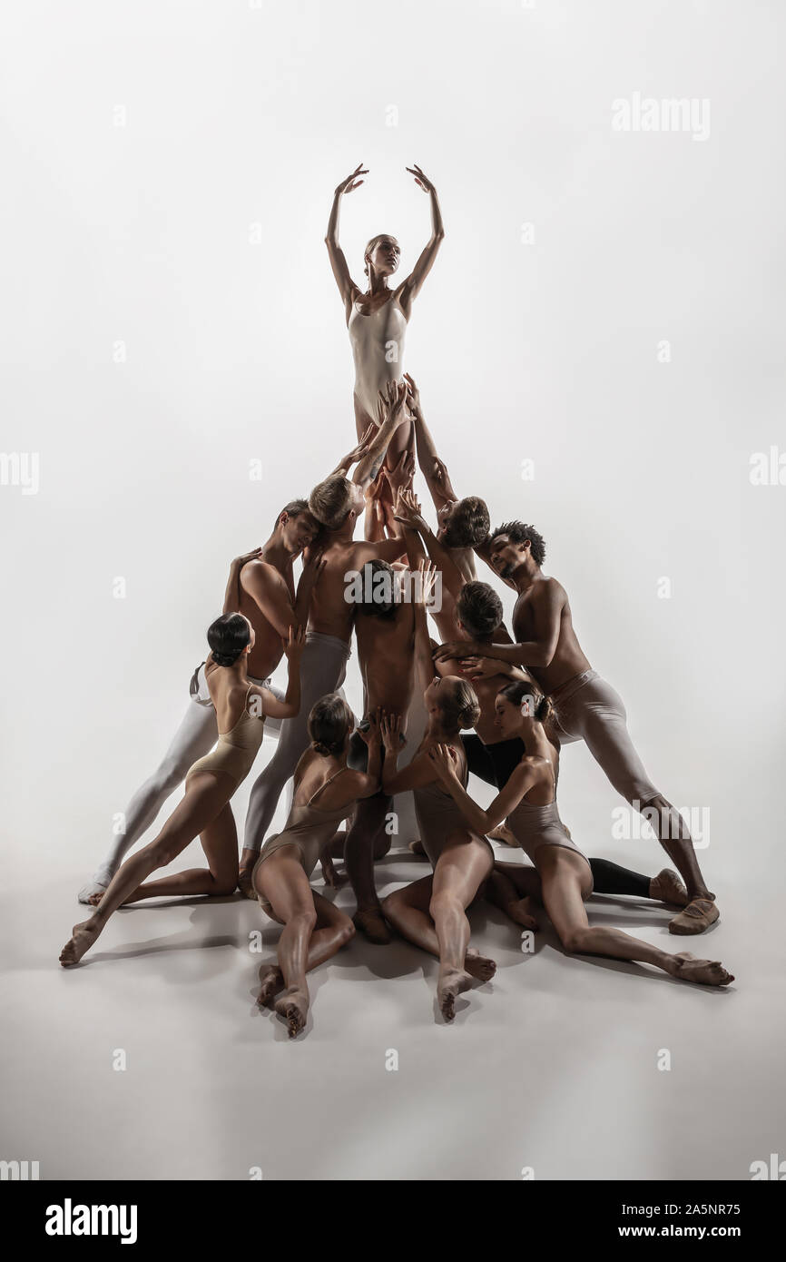 The group of modern ballet dancers. Contemporary art ballet. Young flexible  athletic men and women in ballet tights. Studio shot isolated on white  background. Negative space Stock Photo - Alamy