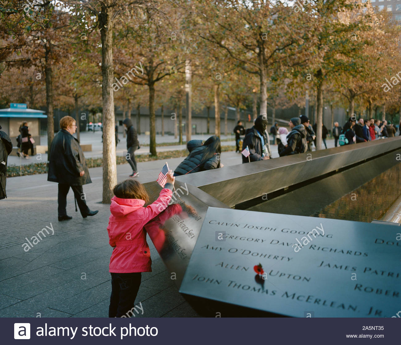 Girl trying to put a USA flag on the National September 11 Memorial, New York City Stock Photo