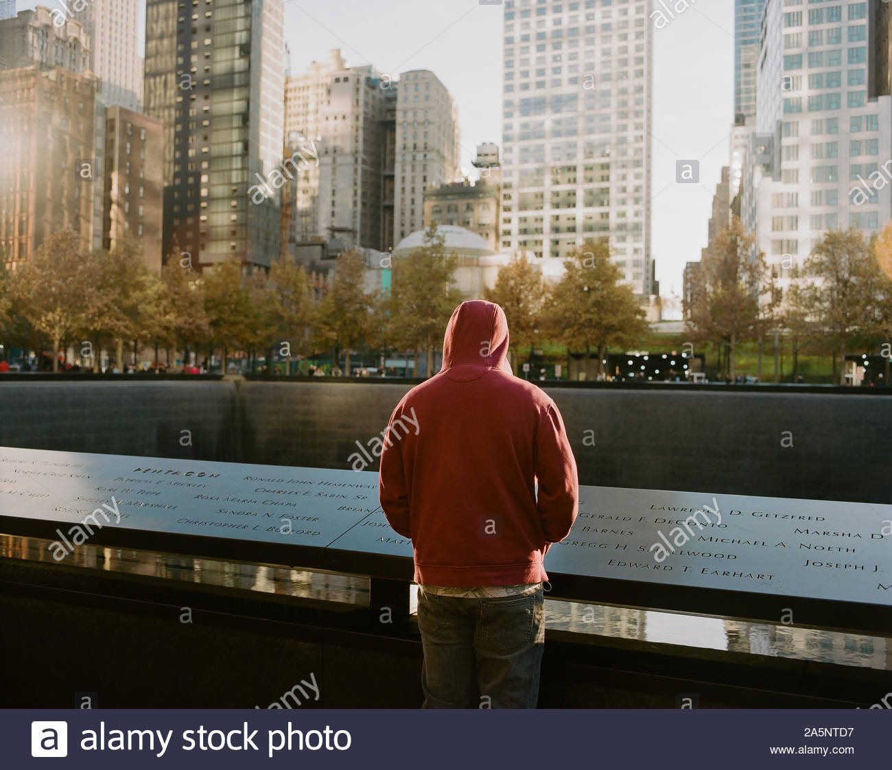 Man watching the northern pool of the National September 11 Memorial, New York City Stock Photo