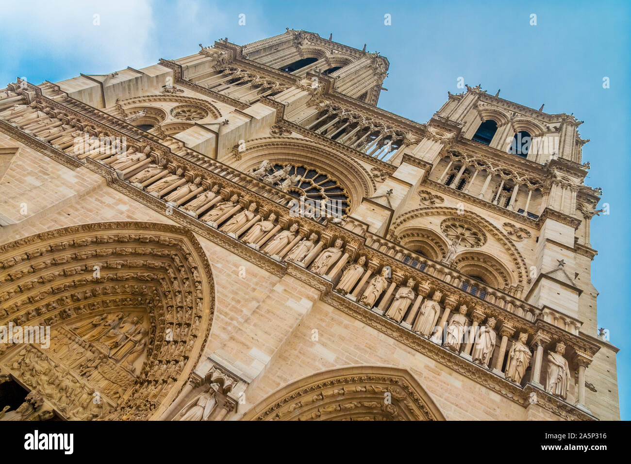Slanted view of the famous west façade of Notre-Dame cathedral on the Île de la Cité in Paris with a close-up of the Gallery of Kings, a row of 28... Stock Photo