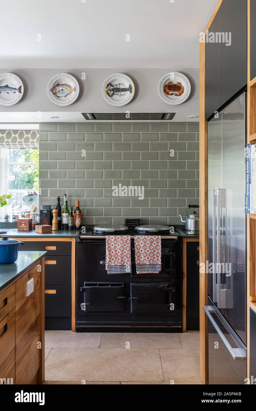 Decorative Plates Above Black Aga With Green Metro Tiles In Bespoke Kitchen By Dominic Ash Stock Photo Alamy