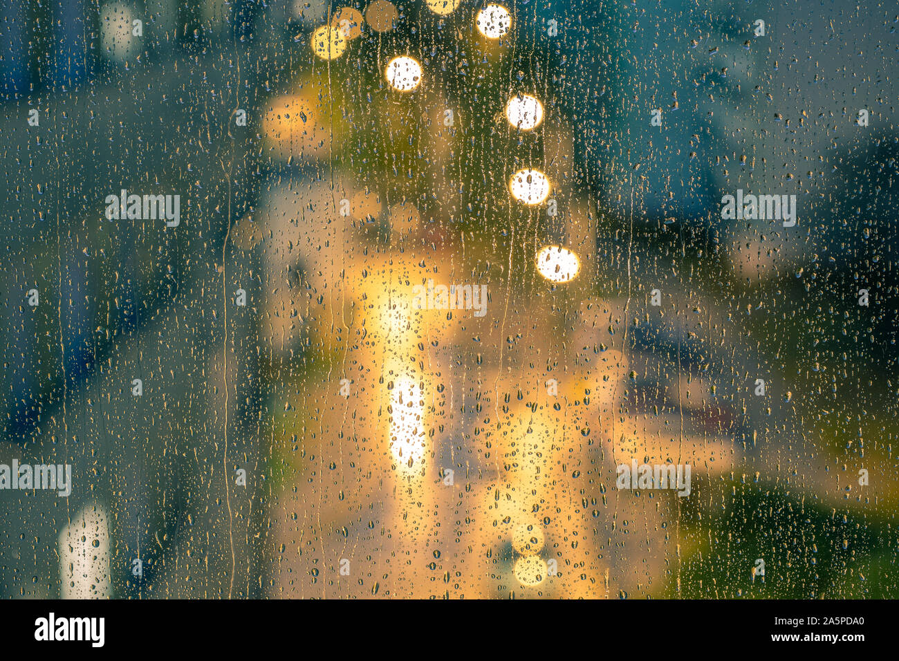 Water drops on the window pane, glass. Lights of the city. Bokeh - abstract background. Stock Photo