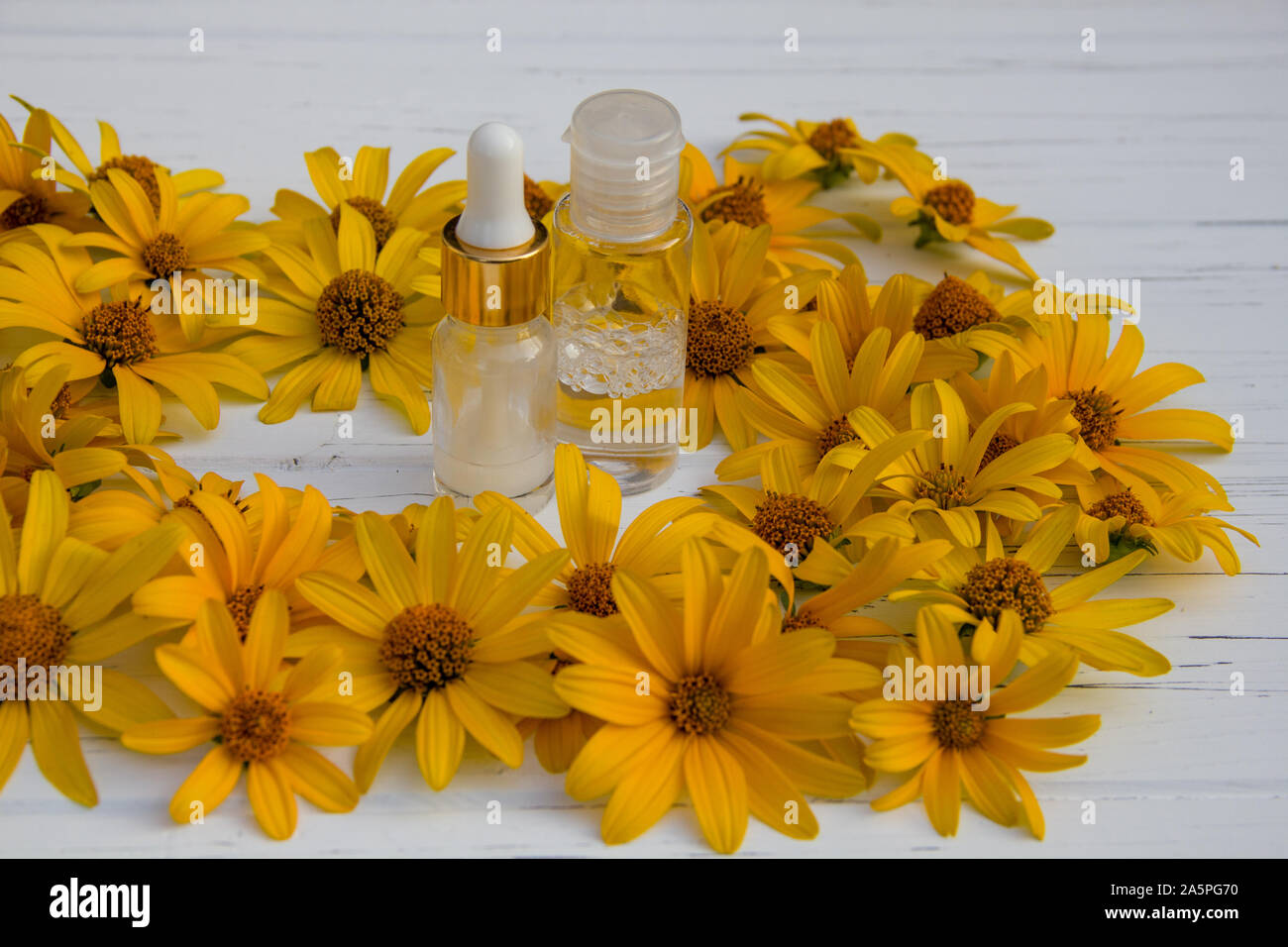 yellow flowers and white cosmetic cream in a bottle and tonic on a wooden light background Stock Photo