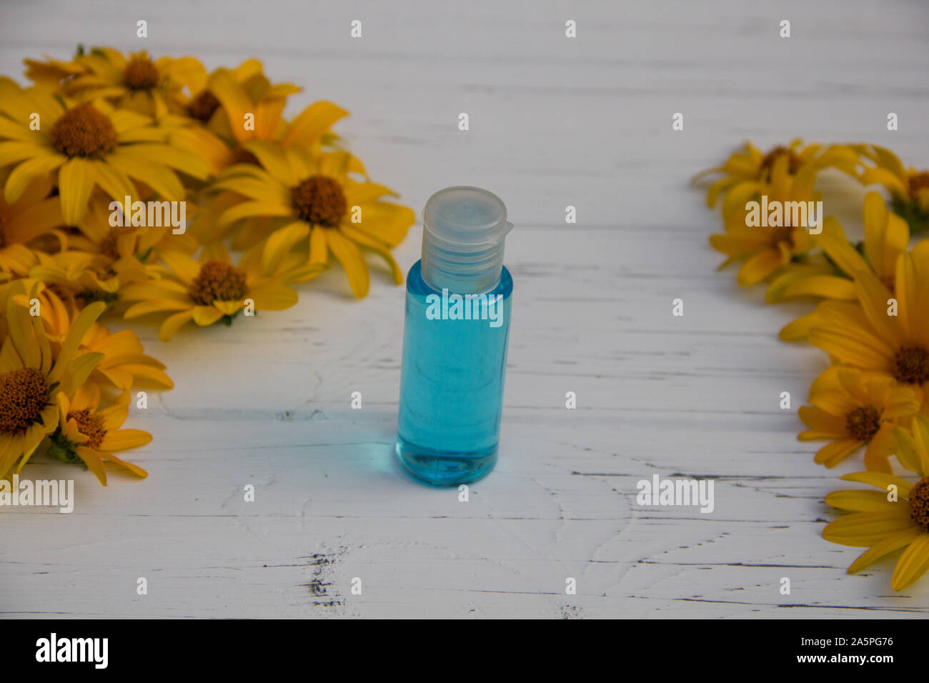 yellow flowers and blue tonic in a bottle on a wooden light background Stock Photo
