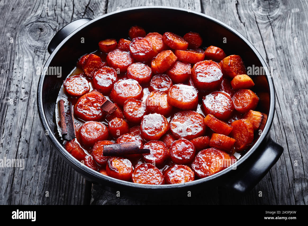 candied yams, thanksgiving sweet potatoes cooked with cinnamon, brown sugar and butter in a black ceramic dish, horizontal view from above Stock Photo