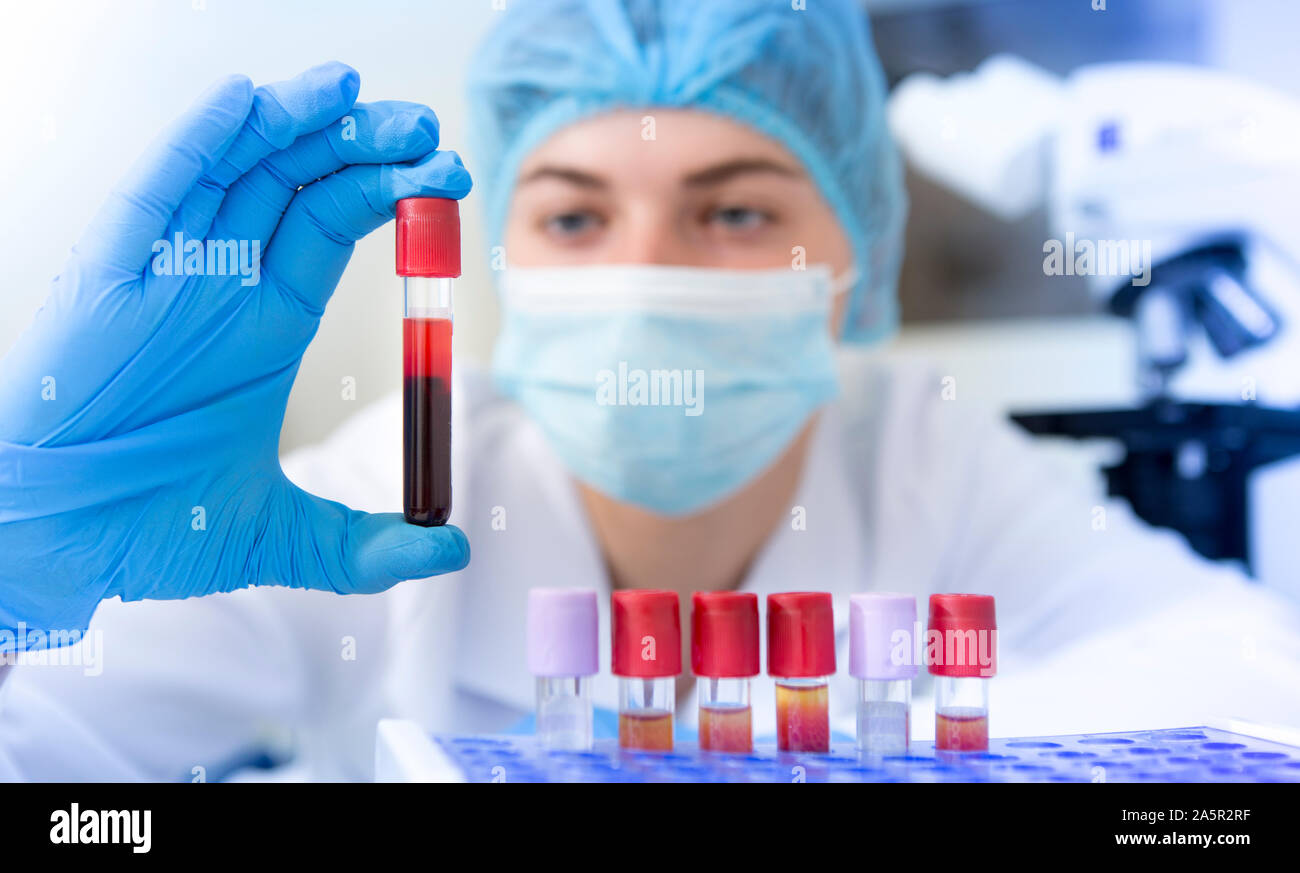 Woman scientist holding blood sample tube from a rack Stock Photo