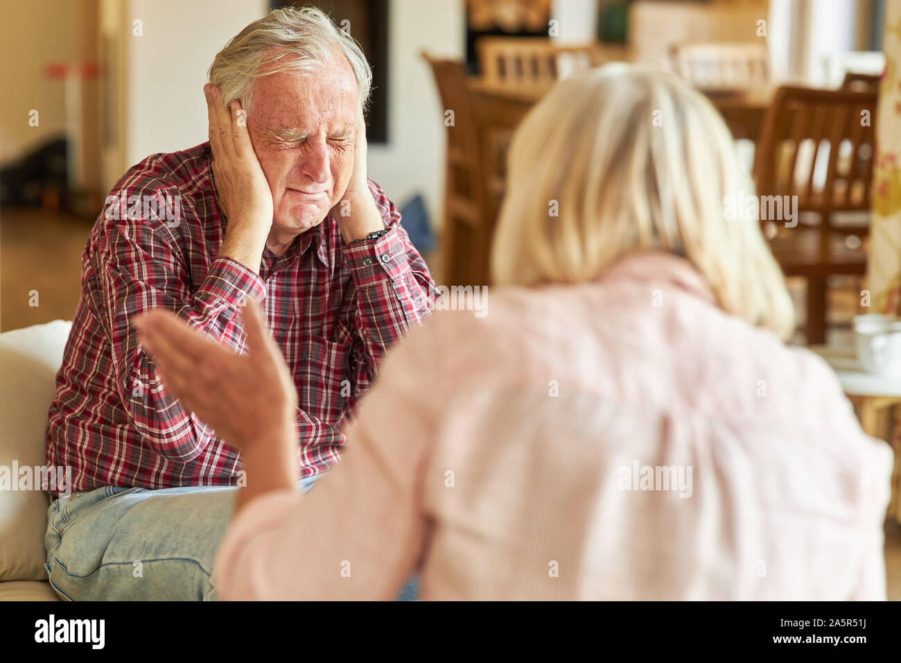 Senior man covers his ears during a rage or quarrel Stock Photo