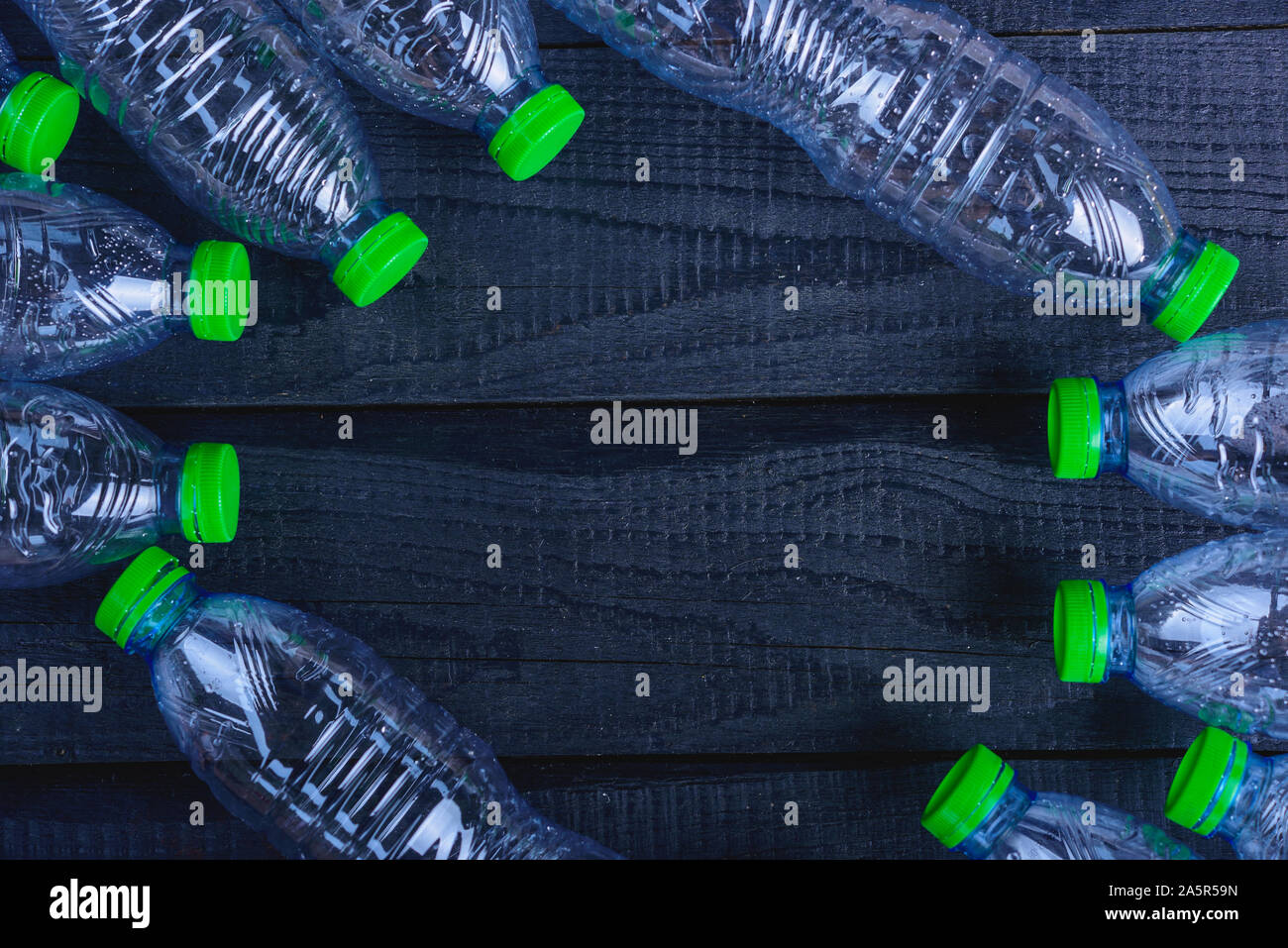 Frame plastic bottles garbage recycled on black wooden, environment concept Stock Photo