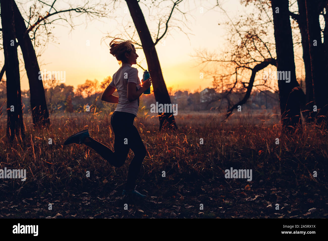 Runner training in autumn park. Woman running with water bottle at sunset. Active lifestyle. Silhouette of slim young girl Stock Photo