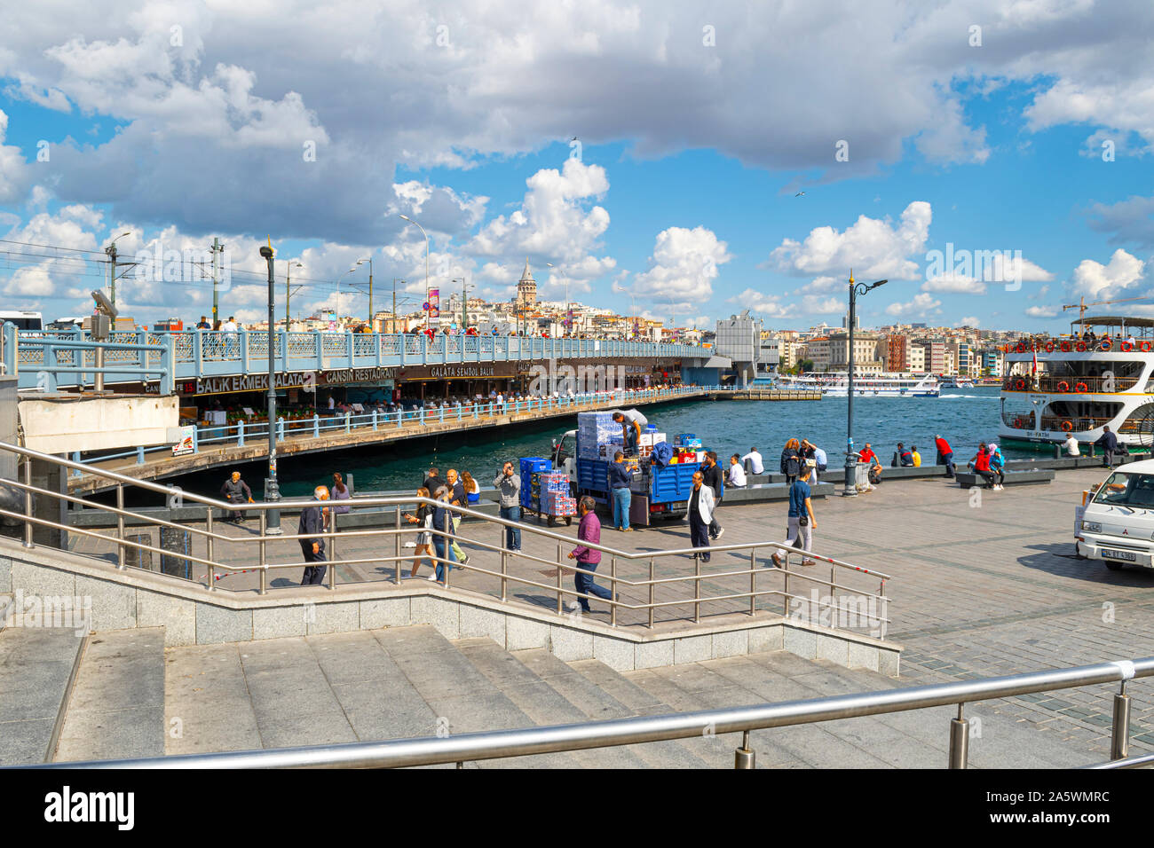 Tourists and local Turks near the ferry port at the Galata Bridge over the Bosphorus, with the Galata Tower in view. Stock Photo