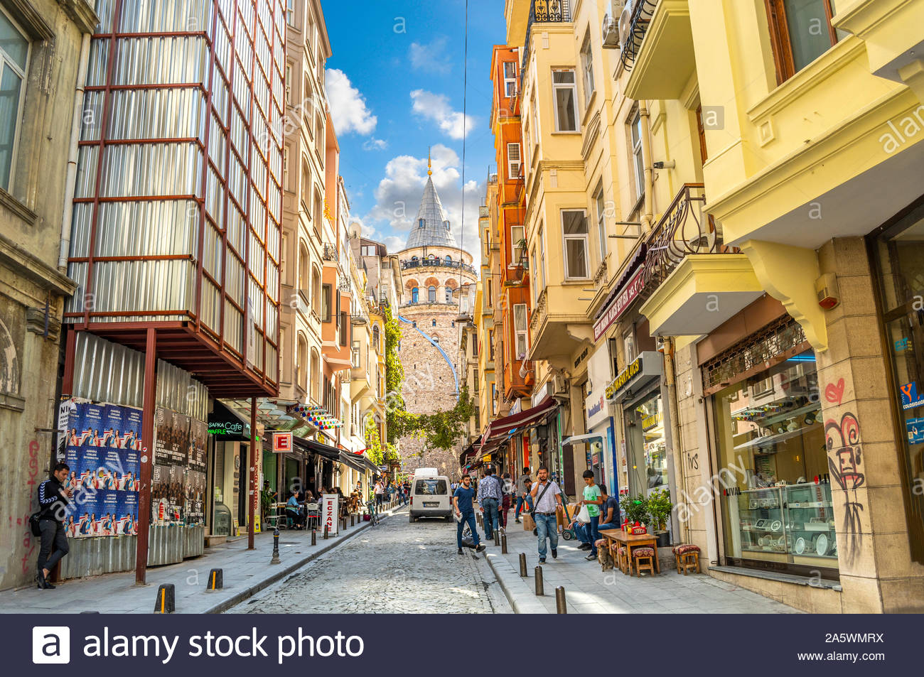 A colorful, busy street of cafes, shops people and a stray cat with the Galata Tower behind, in Istanbul, Turkey. Stock Photo