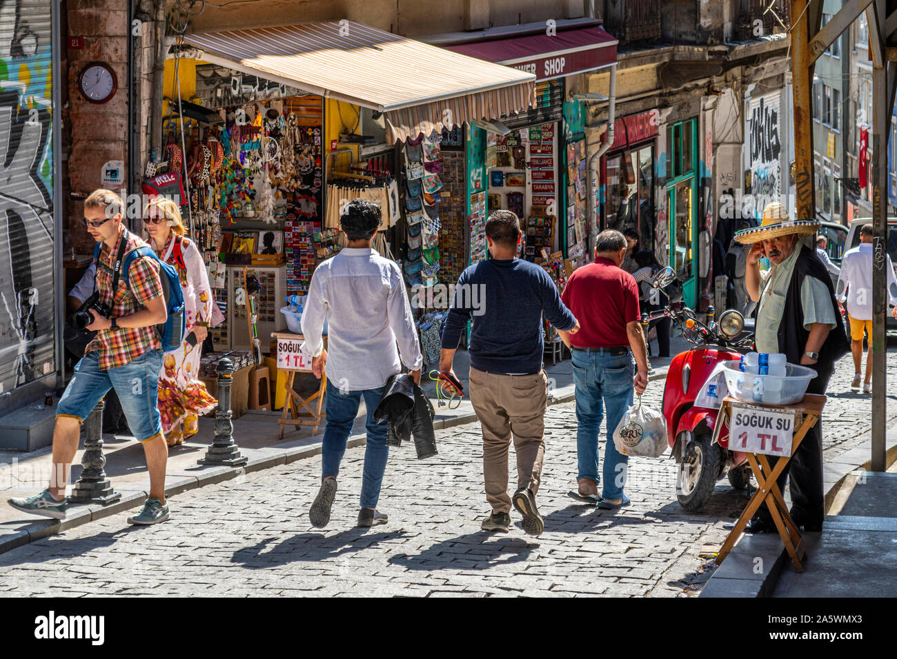A Turk sells bottled water on the sidewalk near souvenir and colorful gift shops in the hilly Galata district of Istanbul Turkey Stock Photo