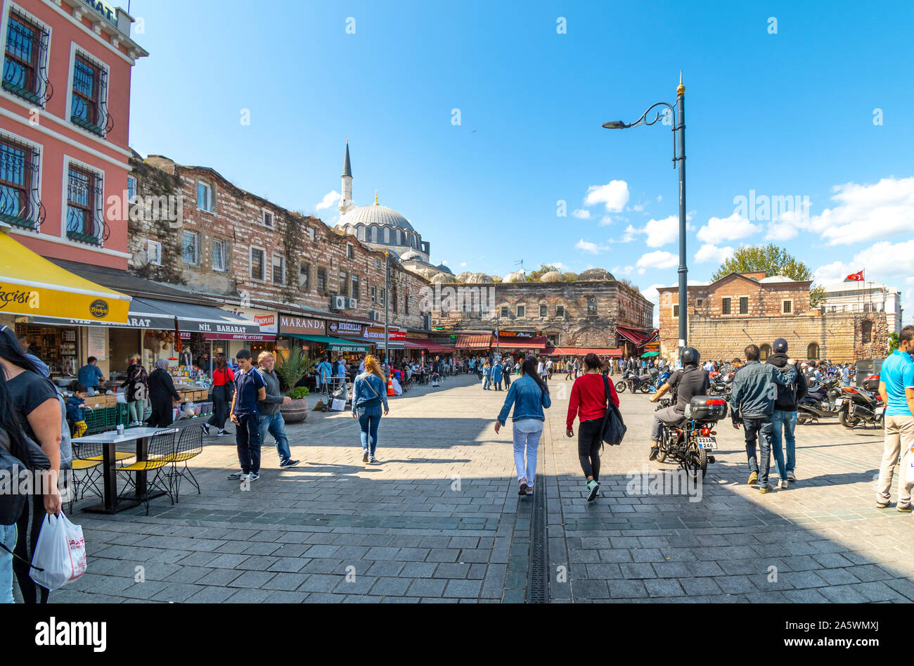 Tourists and Turks enjoy a sunny summer day among the cafes on Eminonu Square with the Yeni New Mosque in view behind. Stock Photo