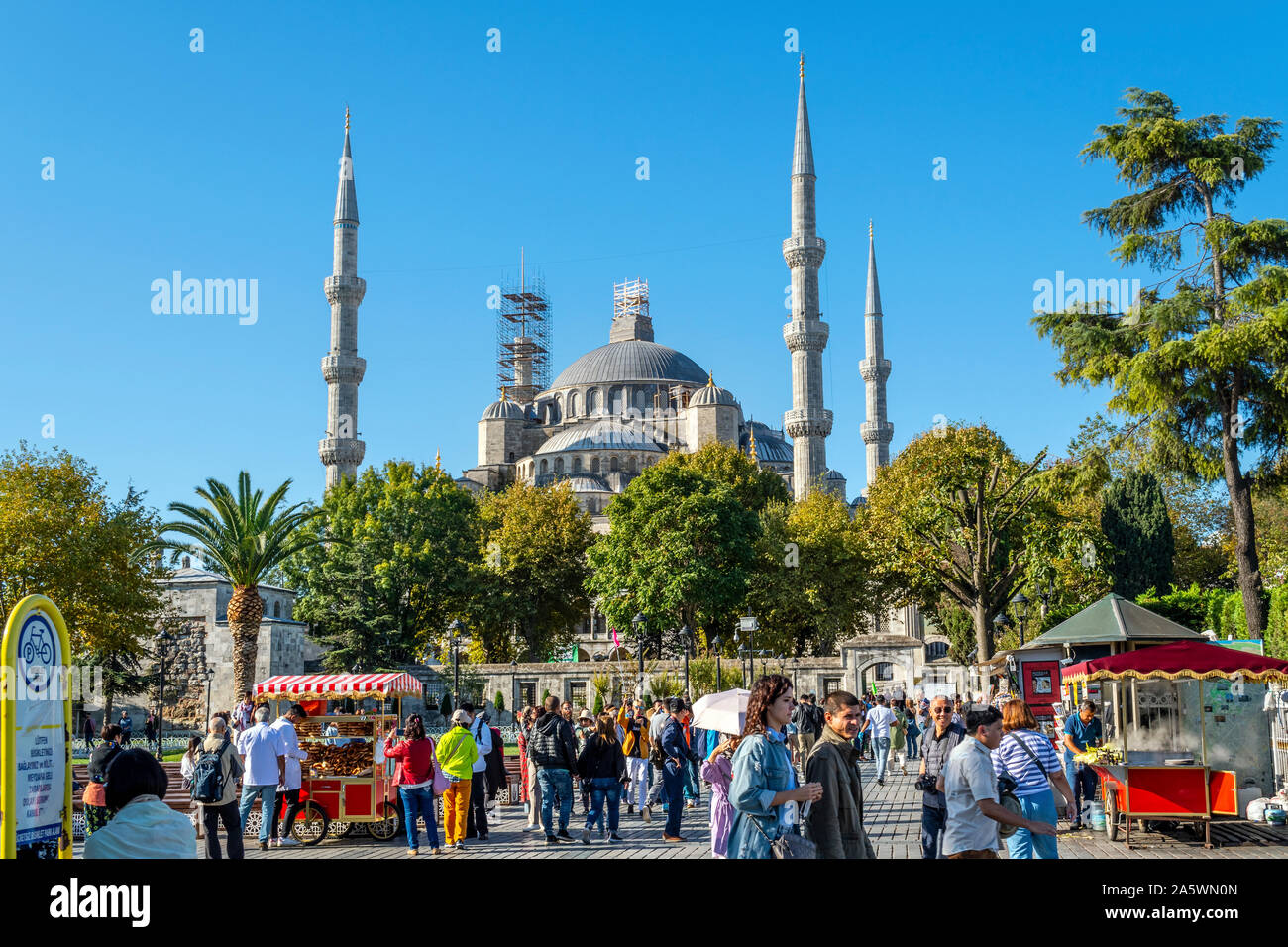 Tourists and local Turks enjoy a sunny day in Sultanahmet Square among the roasted corn cob food vendor stands and the Blue Mosque behind Stock Photo