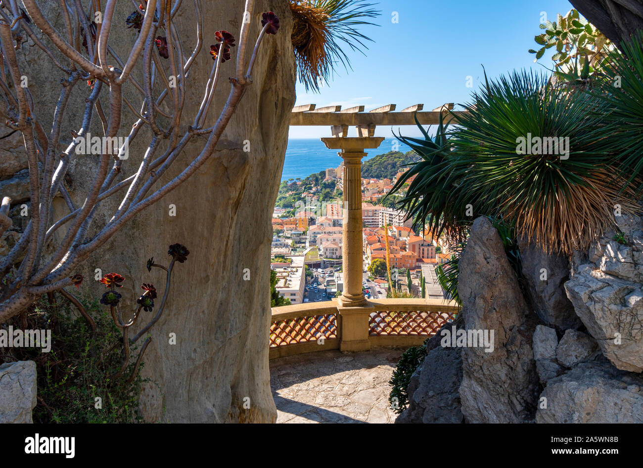 View of the Mediterranean Sea and the city of Monte Carlo, Monaco, between columns from the terrace at the hillside exotic gardens. Stock Photo