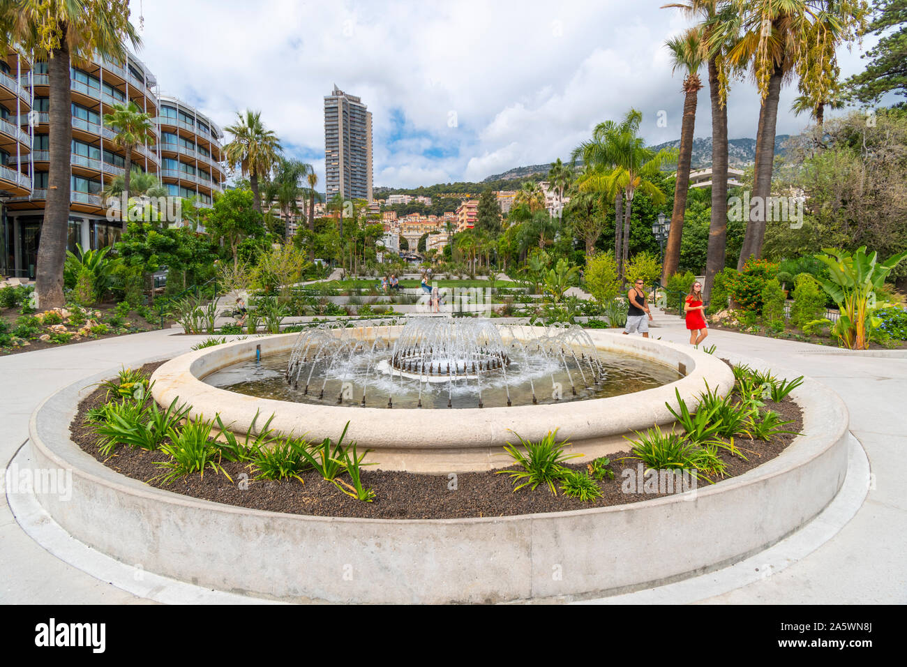 The sloping, landscaped Casino Gardens and water fountain designed by Adouard Andre, with the city behind in Monte Carlo, Monaco. Stock Photo