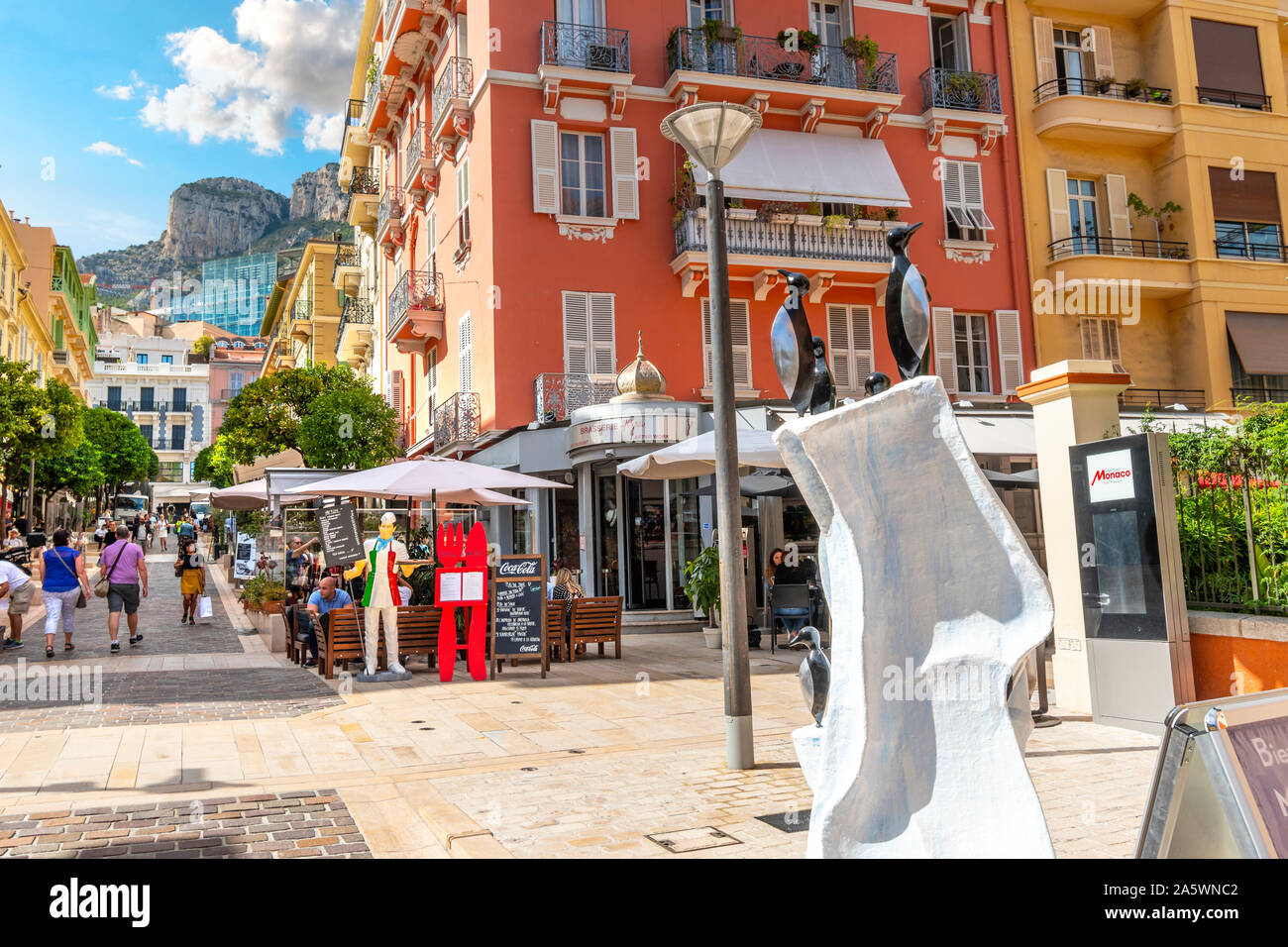 Tourists and local Monegasque enjoy a sunny summer day shopping and dining in Monte Carlo, Monaco, with the steep mountains in the distance. Stock Photo