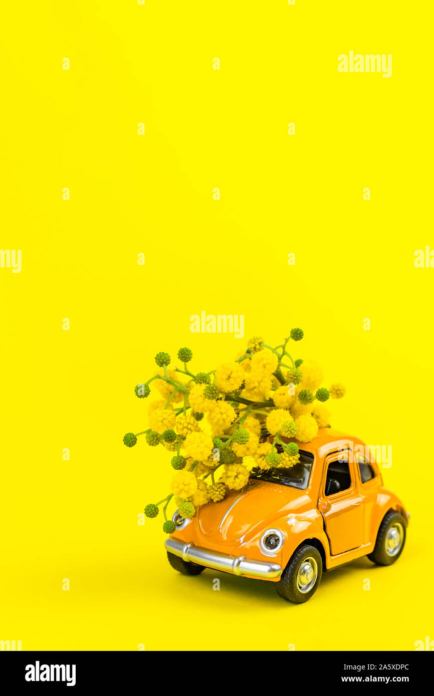Moscow, Russia - February 23, 2019: 8 March International Women's Day card with toy model of retro car delivering bouquet of mimosa flowers on yellow Stock Photo
