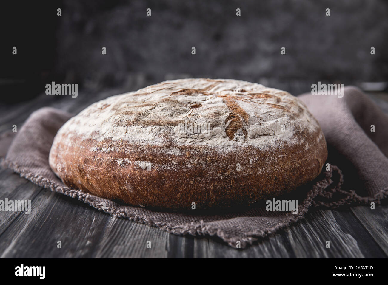 A homemade round levain bread with rye and wheat flour. that is laid on a dark wooden table, with a dark background. There is a brown soft linen cloth Stock Photo