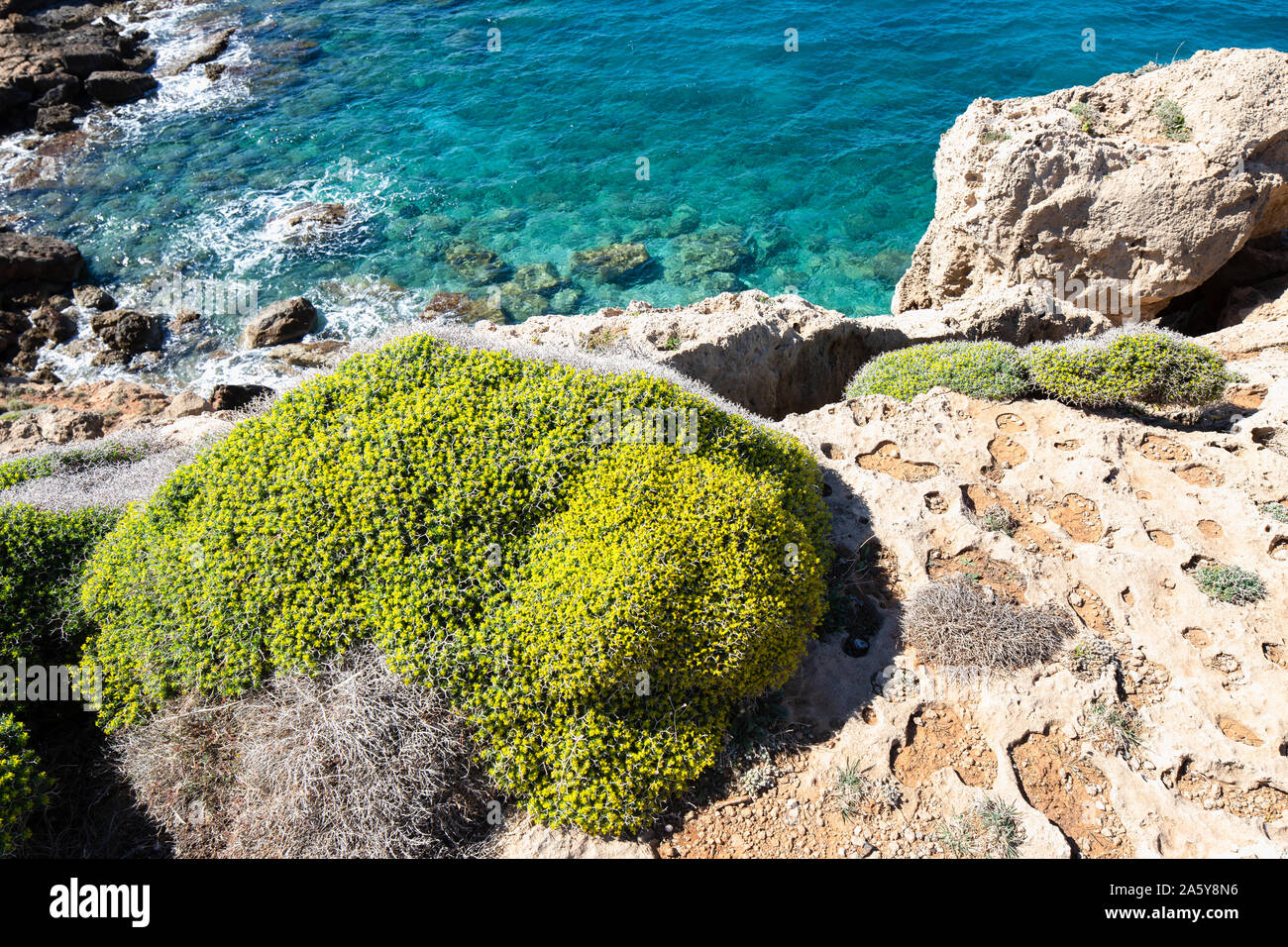 Crete landscape, blue sea and sky on a sunny day in background, rocks and green hills. Stock Photo